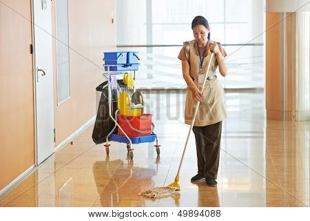Limpador empregada mulher trabalhadora com esfregão de uniforme limpando chão de passagem ou corredor corredor de busines