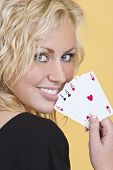 picture of playing card  - A beautiful young woman holding a hand of four aces showing them to the camera and looking happy - JPG