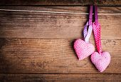 stock photo of wood craft  - Crochet valentine hearts handing on the rope - JPG