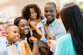 stock photo of cashiers  - Happy shopping family at the cashier paying for their purchases - JPG