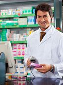 image of barcode  - portrait of mid adult pharmacist scanning medicine with barcode reader - JPG