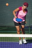 foto of pickleball  - Image of colorfully clad senior woman hitting a pickleball during a match - JPG
