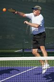 pic of pickleball  - Senior pickleball player hitting a overhead smash while gritting teeth - JPG