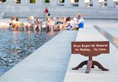image of disrespect  - Tourists bathing feet by sign warning against disrespecting World War II Memorial is a national memorial dedicated to Americans who served in the armed forces and as civilians during World War II - JPG