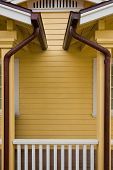 stock photo of downspouts  - Matched copper rain gutters on the porches of a duplex - JPG