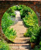 stock photo of english cottage garden  - Pathway through an old garden wall in bright sunshine - JPG