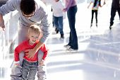 image of skate  - young father teaching his little smiling son ice skating and having fun time - JPG