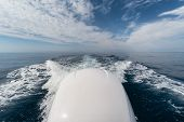 picture of outboard  - boat wake and outboard engine against blue sky - JPG