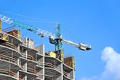 stock photo of formwork  - Crane and building construction site against blue sky - JPG