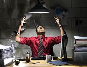 stock photo of indian money  - An image of an Indian businessman with a red shirt and tie behind a desk in a basement office - JPG