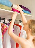 stock photo of wardrobe  - Young woman chooses clothes in the wardrobe closet at home - JPG