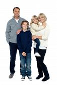 stock photo of pullovers  - Full length portrait of a happy family posing in trendy winter wear outfits - JPG