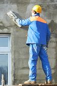 stock photo of putty  - Male builder plastering exterior wall during industrial facade building with putty knife float - JPG