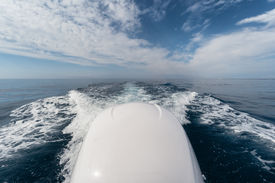 picture of outboard engine  - boat wake and outboard engine against blue sky - JPG