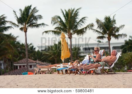 Senior Couple Relaxes In Beach Chairs At Florida Resort