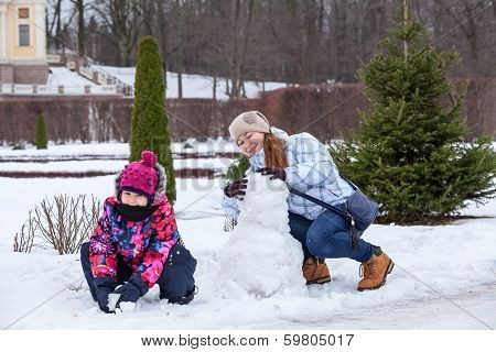 Young Mother And Daughter Making Snowman With Snow In Winter Park