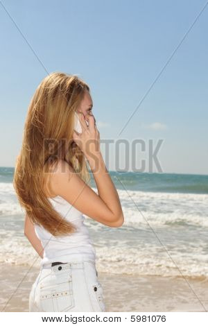Woman Talking On Phone On The Beach