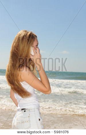Woman Talking On Phone On The Beach