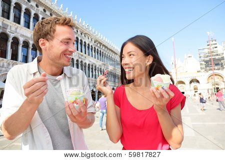 Couple eating ice cream on vacation travel in Venice, Italy. Smiling happy young couple in love having fun eating italian gelato food outdoors during holidays on San Marco Square, Venice, Italy