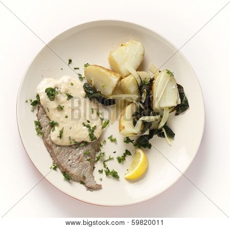 Fried and peppered escalope of veal served with  potatoes mixed with wilted chard and a creamy gravy, all garnished with chopped herbs and served with a lemon wedge, from above