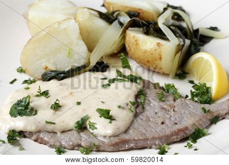Grilled escalope of veal with a creamy gravy, boiled potatoes with wilted chard, garnished with fresh herbs