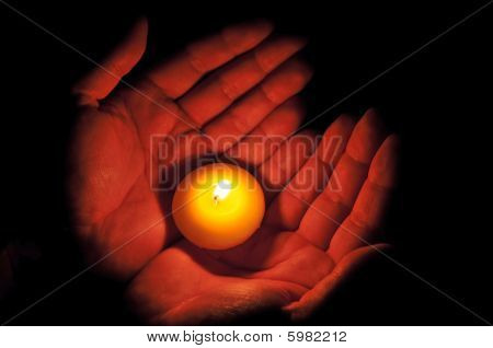 Hands holding one candle