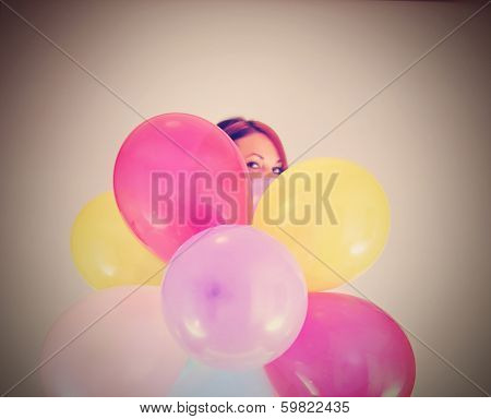 a pretty girl hiding behind a bunch of balloons done with a retro vintage instagram filter (focus on the balloons)