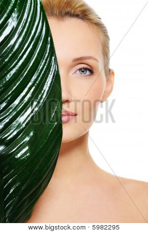 Face Of Woman Hiding Behind The Big Green Leaf