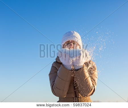 Young girl blows away snow off hands