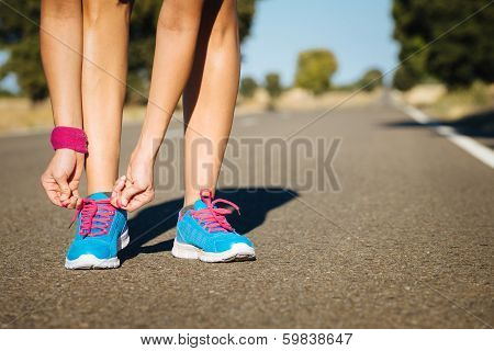 Female Athlete Tying Sportshoes Laces For Running