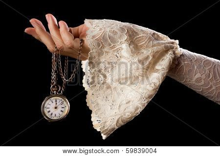 Female hand in lace sleeve holding an antique pocket watch on a chain