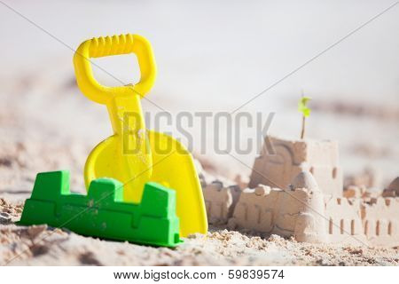 Sandcastle and variety of colorful beach toys