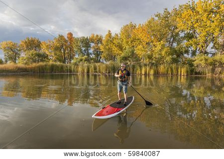 senior male paddler enjoying workout on stand up paddleboard (SUP), calm lake in Colorado, fall colors