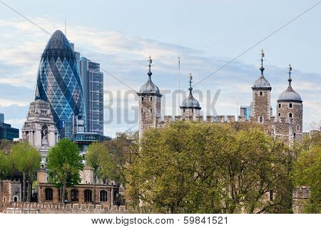 The Tower of London and the 30 St Mary Axe skyscraper aka the Gherkin, England, the UK. The historic Royal Palace and Fortress next to the financial district