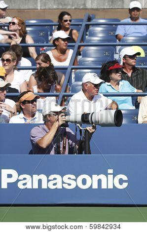 Professional photographer and spectators during US Open 2013