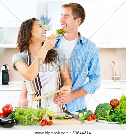 Cooking. Happy Couple Cooking Together - Man and Woman in their Kitchen at home Preparing Vegetable Salad. Diet. Dieting. Healthy Food