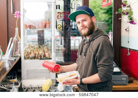 Hotdog - friendly salesman and fresh ingredients in a fast food snack bar