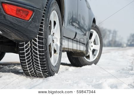 Car with winter tyres installed on light alloy wheels in snowy outdoors road