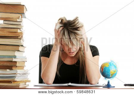 Young woman studying at the desk being tired, isolated on white