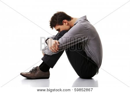 Depressed and sad young business man. Isolated on white background.