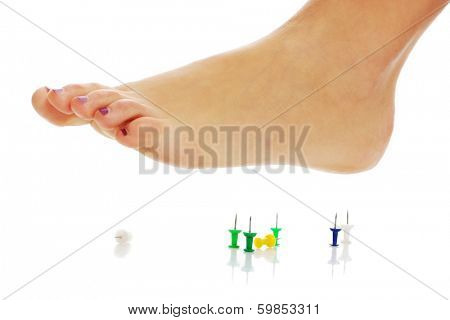 Female foot above pushpin, isolated on white background