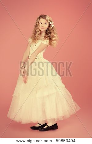 Full length portrait of a girl with beautiful gentle appearance in white festive dress. Over pink background.