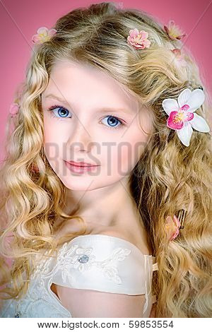 Portrait of a girl with beautiful gentle appearance in white festive dress. Over pink background.