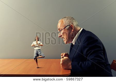 big angry boss looking at calm meditation worker