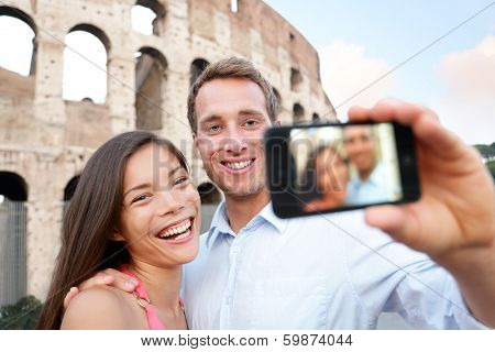 Happy travel couple taking selife by Coliseum, Rome, Italy. Smiling young romantic couple traveling in Europe taking self portrait photo with smartphone camera in front of Colosseum. Man and woman.