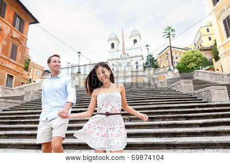 Happy romantic couple holding hands on Spanish Steps in Rome, Italy. Joyful young interracial couple walking on the travel landmark tourist attraction icon during their romance Europe holiday vacation