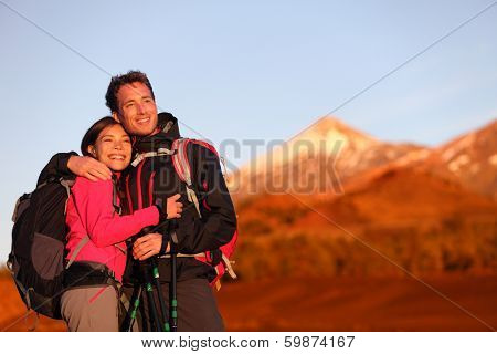 Happy couple hiking enjoying looking at view embracing in love. Hiker man and woman wearing backpacks enjoying sunset during hike on mountain volcano Teide, Tenerife, Canary Islands, Spain.