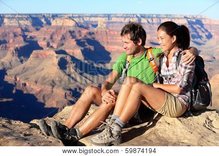 Hiking couple portrait - hikers in Grand Canyon enjoying view of nature landscape smiling happy. Young couple trekking, relaxing after hike on south rim of Grand Canyon, Arizona, USA. Man and woman.