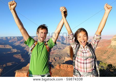Happy people celebrating cheering in Grand Canyon. Young multiethnic couple on hiking travel excited and elated in Grand Canyon, south rim, Arizona, USA. Asian woman and Caucasian man.