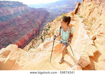 Hiker woman hiking in Grand Canyon walking with hiking poles. Healthy active lifestyle image of hiking young multiracial female hiker in Grand Canyon, South Rim, Arizona, USA.